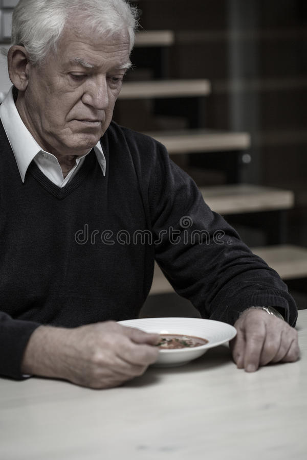 Dinner at home. Older depressed alone man eating dinner at home royalty free stock photos