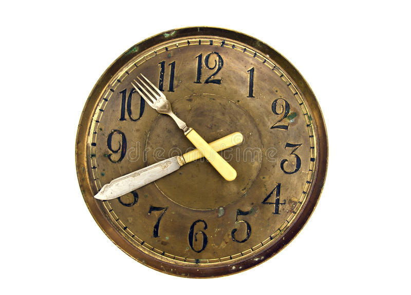 Dinner lunch time - old clock face dial with fork and knife arrows. Dinner time concept - old clock face dial with fork and knife arrows isolated on white royalty free stock images