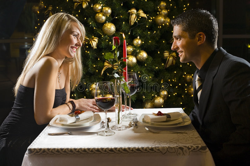 Dinner party. Couple at restaurant on dinner party. They're looking at each other and smiling