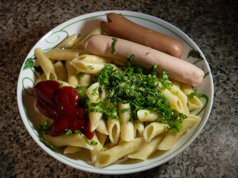 Dinner, pasta and sausages are in the plate stock photo