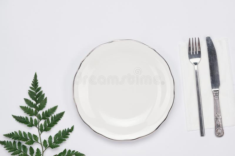 Dinner plate setting top view. Empty plate and silverware set on. Wooden table stock photo