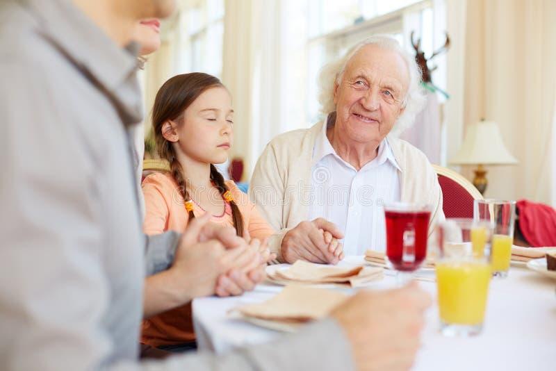 Dinner pray. Portrait of smiling senior men at festive table during pray stock photography