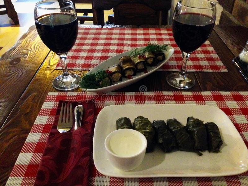 Dinner in a restaurant. Red wine in glasses, dolma. Eggplant. Eastern cuisine royalty free stock image
