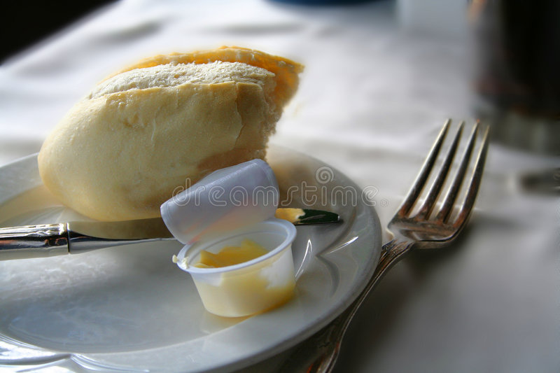 Dinner roll. Loaf of bread with butter on a plate royalty free stock photo