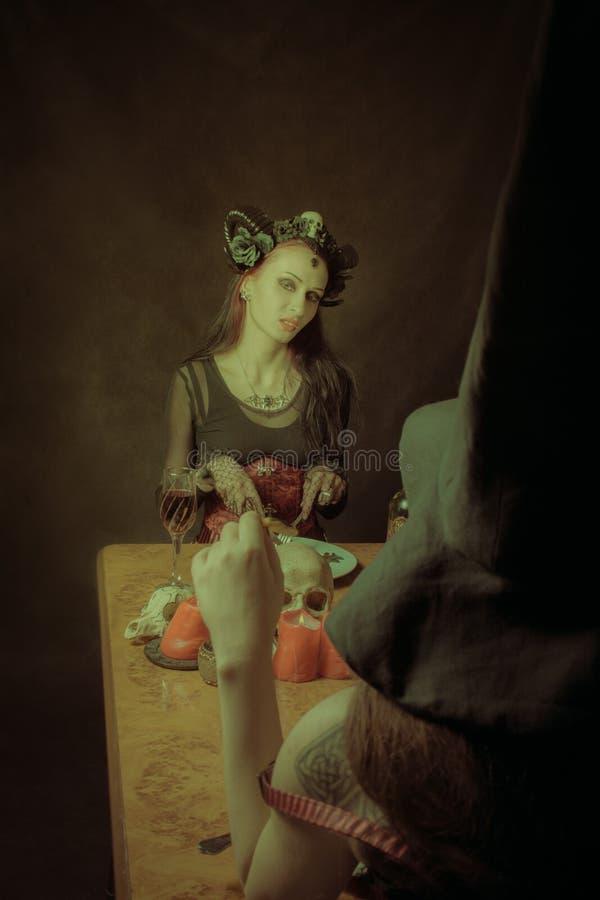 Dinner with Satan. Beautiful horned lady having dinner over dark background stock photos