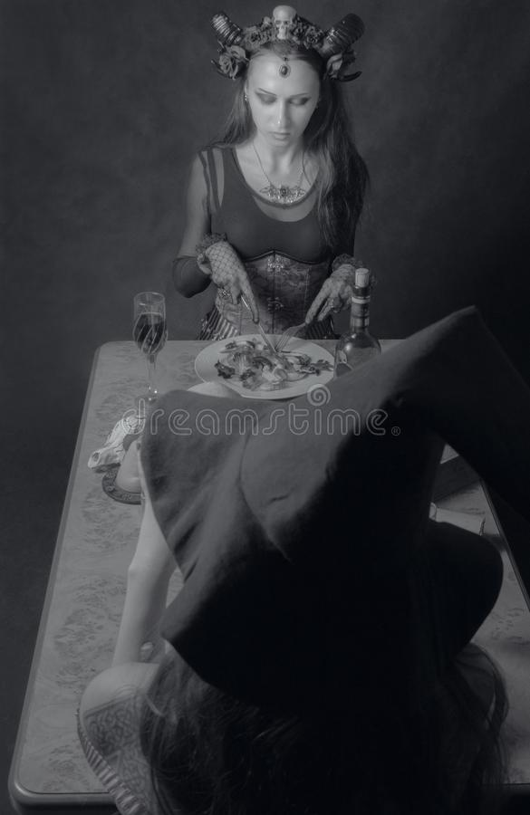 Dinner with Satan. Horned gothic girl having dinner over dark background stock photos