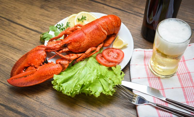 Dinner seafood lobster steamed on plate seafood with lemon salad lettuce vegetable and tomato / Beer glass on table royalty free stock photography