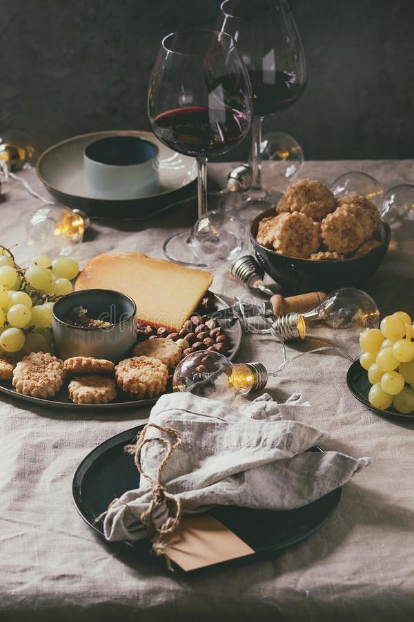 Dinner set table. Home dinner table set with wine, cheese plate, appetizers and empty plate with cloth napkin royalty free stock photo