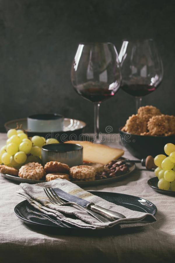 Dinner set table. Home dinner table set with wine, cheese plate, appetizers and empty plate with cloth napkin stock photo