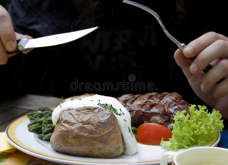 Dinner with steak, asparagus and baked potato royalty free stock image