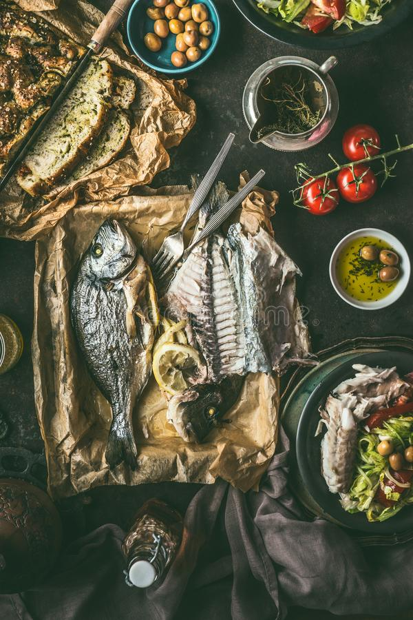 Dinner table with backed dorado fish, salad and homemade bread on dark rustic table, top view. Mediterranean lunch or dinner. Healthy food stock images