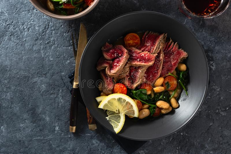 Dinner table. Beef steak with white beans, spinach and tomatoes on dark stone background with glass red wine top view with free. Dinner table. Beef steak with royalty free stock image