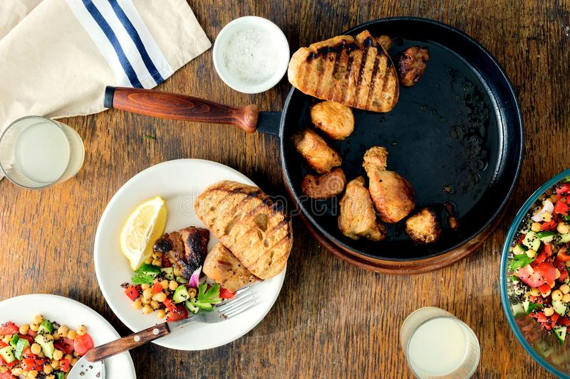 Frying pan fried meat homemade lemonade salad chickpeas and vegetables. Dinner table concept. Frying pan with fried meat on wooden table with homemade lemonade royalty free stock photos