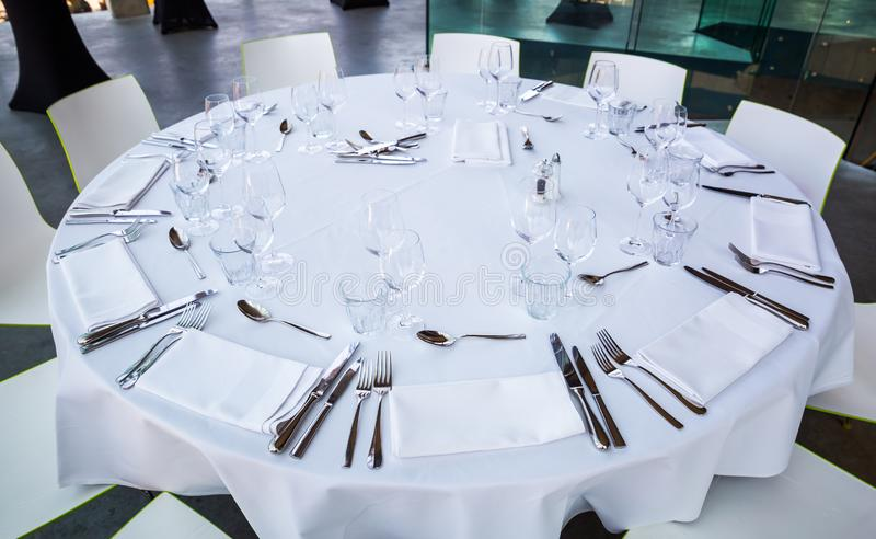 Dinner table with empty glasses and plates stock image