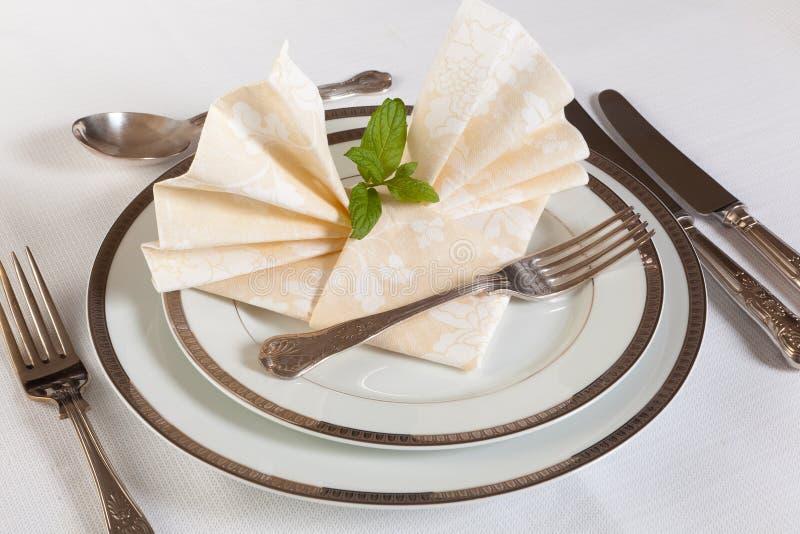 Dinner table with festive napkins. Elegant dinner table with vintage cutlery and festive napkins stock photography