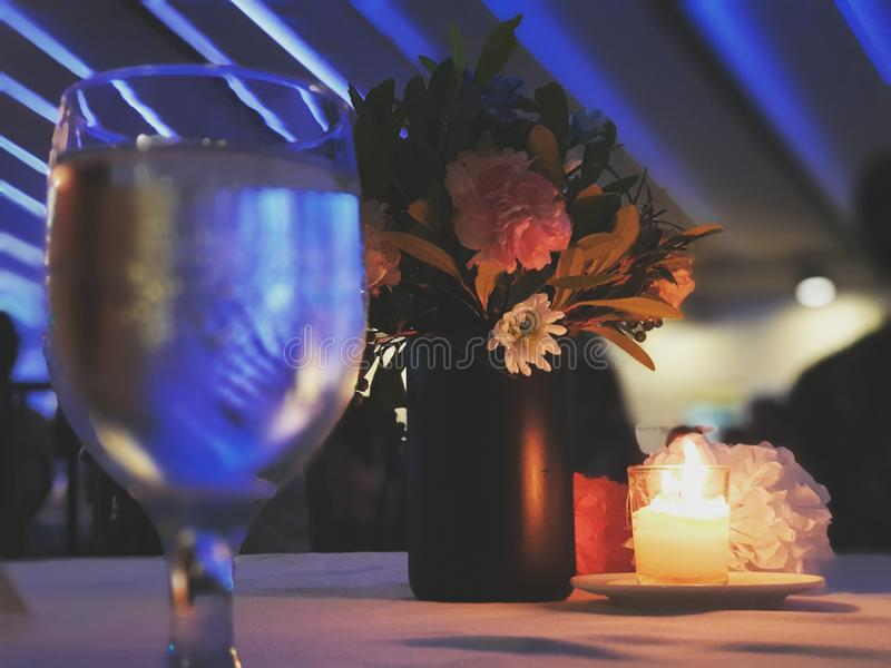 Ready for a Dinner Date?. A dinner table with a glass of water and a romantic flower and candle as a centerpiece royalty free stock images