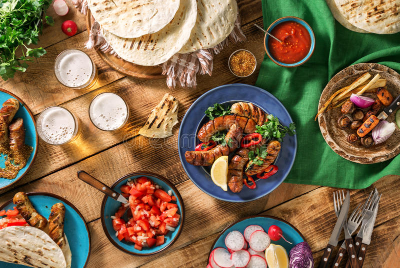 Dinner table with grilled sausage, tortilla, beer and different royalty free stock images