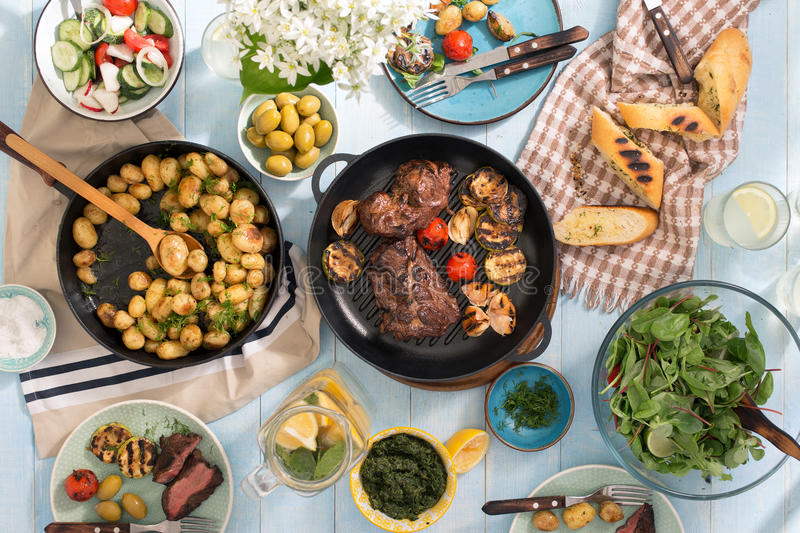 Dinner table with grilled steak, vegetables, potatoes, salad, sn. Grilled steak, grilled vegetables, potatoes, salad, different snacks and homemade lemonade on stock photos