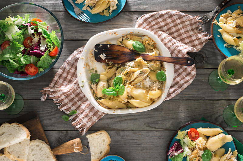 Dinner table with pasta, fresh salad and white wine. Dinner table with Italian pasta, fresh salad and wine on wooden table, top view. Rustic style. Dinner party stock photo