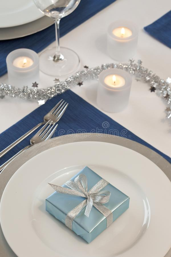 Dinner table place setting with candles and gift decorated for Hanukkah party. Traditional Jewish holidays home celebrations decor stock photo