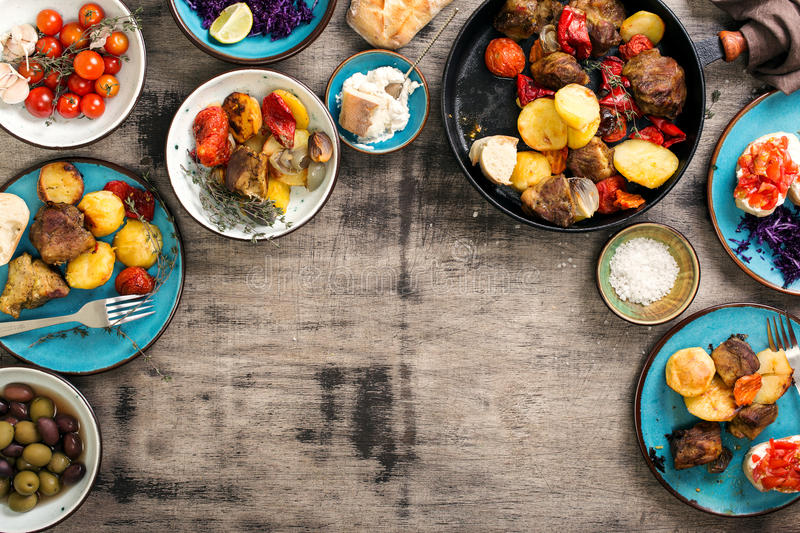 Dinner table with variety food, top view. Dinner table with variety food, fried meat with vegetables in a pan, salad and snacks, top view royalty free stock image