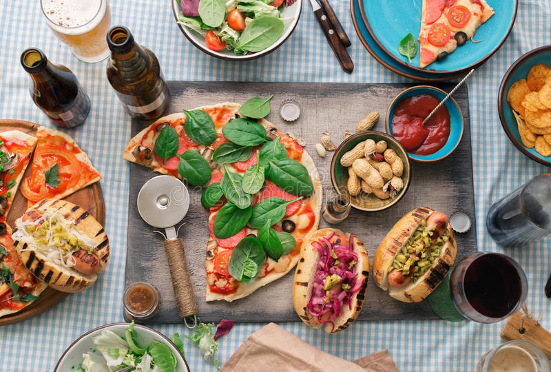 Dinner table with various food for company, top view. Italian pizza, hot dog grilled, salad, red wine, lager and snacks to beer, top view. Dinner table with stock images