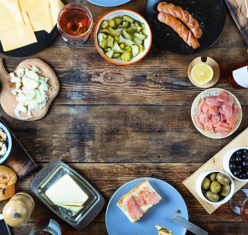 Dinner table. Various snacks and wine. top veiw. Dinner table. Various snacks and wine. Salmon, olives, grilled sausages, buns and other ingredients for hot dogs royalty free stock photography