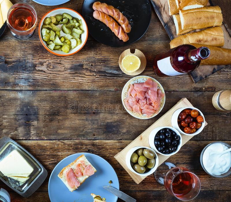 Dinner table. Various snacks and wine. top veiw. Dinner table. Various snacks and wine. Salmon, olives, grilled sausages, buns and other ingredients for hot dogs royalty free stock photo