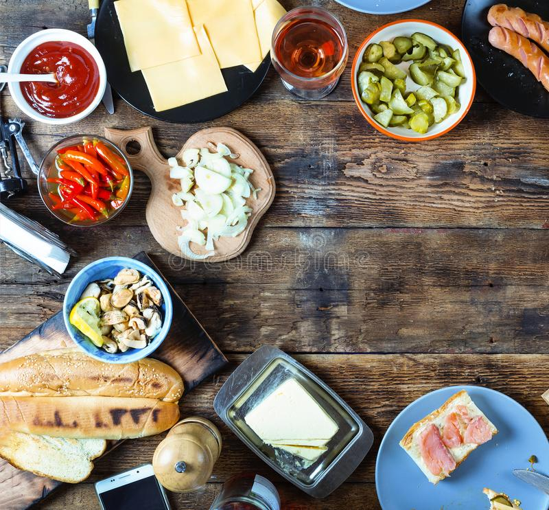 Dinner table. Various snacks and wine. top veiw. Dinner table. Various snacks and wine. Salmon, olives, grilled sausages, buns and other ingredients for hot dogs stock image