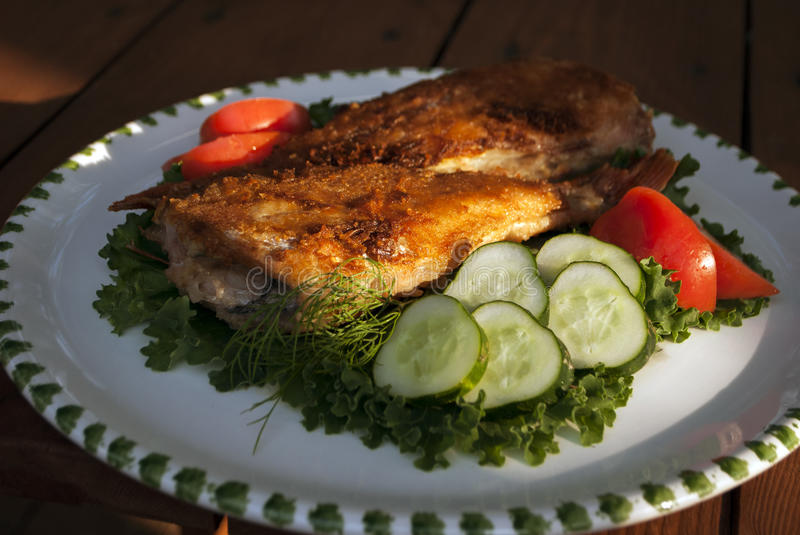Dinner. Tasty fried sea bass with vegetables. Dinner. Photo of tasty fried sea bass with vegetables stock images