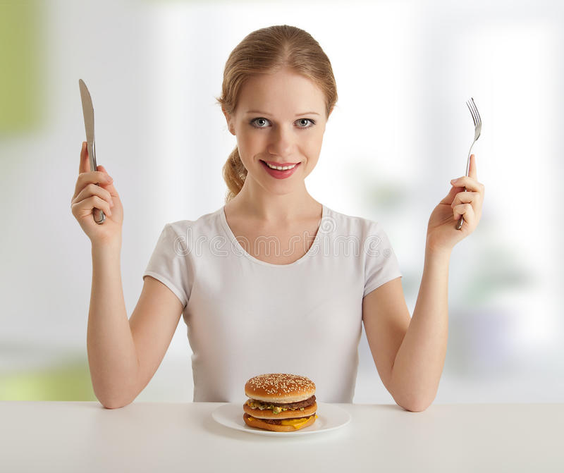 Dinner time.woman and knife, fork, hamburger. Dinner time. pretty young woman with a knife and fork, and hamburger stock image