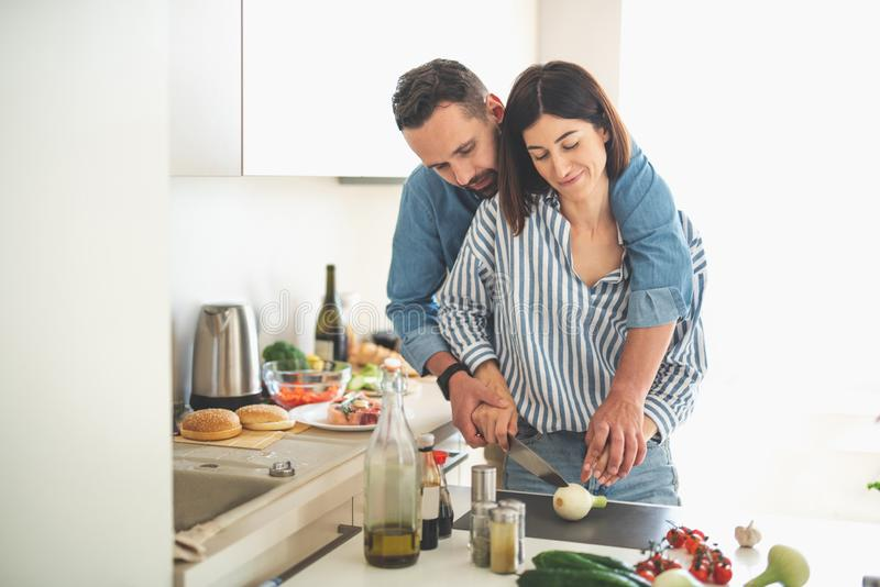 Beautiful young couple cooking together at home royalty free stock photo