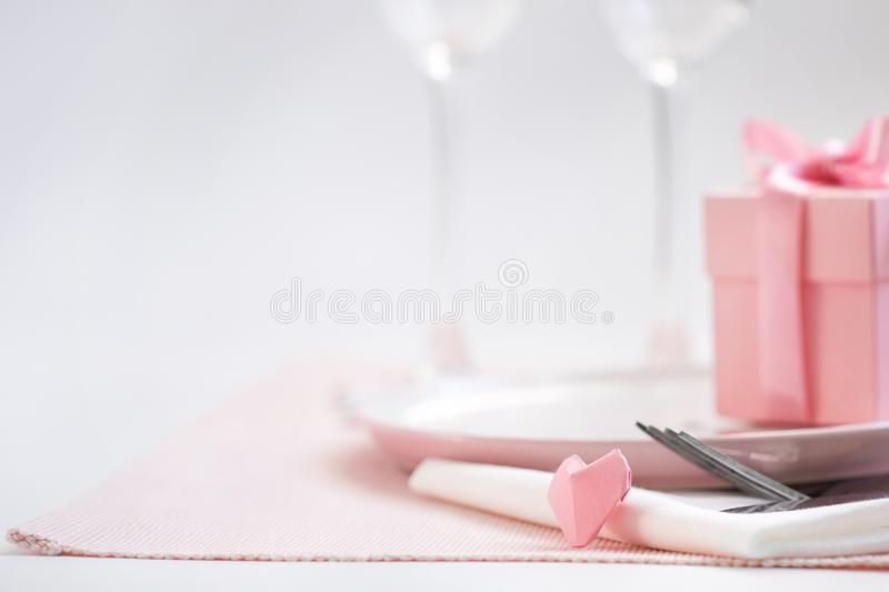 Dinner on Valentine`s day. Pink plate, Cutlery, pair of glasses, gift, heart on the table. stock photo
