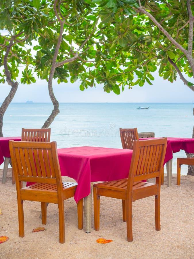 Dinner wooden table set on the beach stock photo