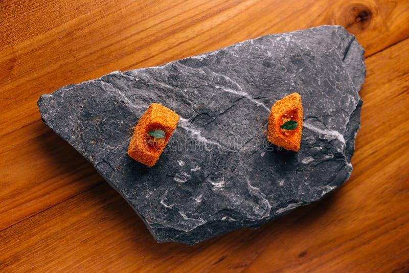 Dinning fino creativo: Los pescados con el desmoche anaranjado del esmalte del color con ikura sirvieron en la placa de piedra fotos de archivo libres de regalías