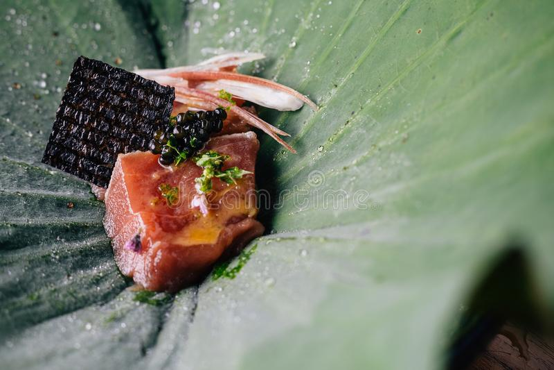 Dinning fino criativo: Feche acima do atum com cobertura do yuzu-miso com caviar preto e o abacate servidos na folha dos lótus foto de stock royalty free