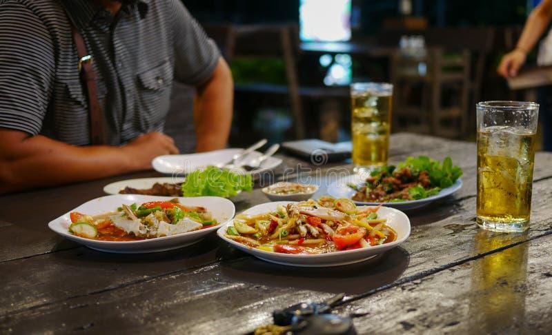 Dinning-Tabelle mit Lebensmittel im Restaurant und zwei Gläser Bier mit Mann sitzen im Gegenteil lizenzfreie stockfotografie