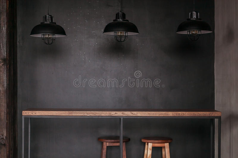Dinning table set in loft style dining room with black lamps.  stock photo