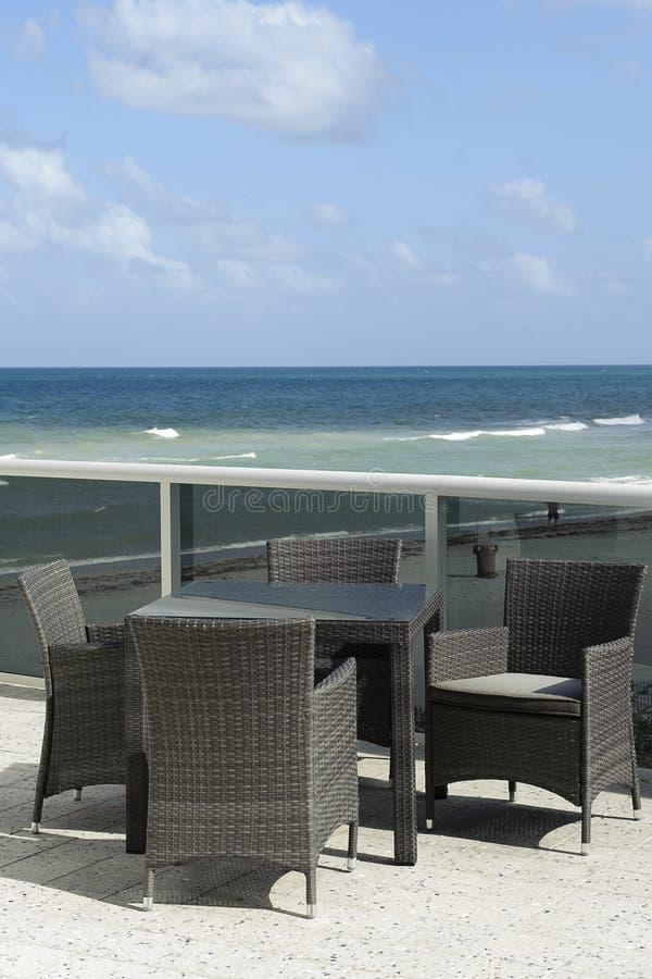 Dinning uppsättning för utomhus- vide- uteplats som förbiser havet arkivbild