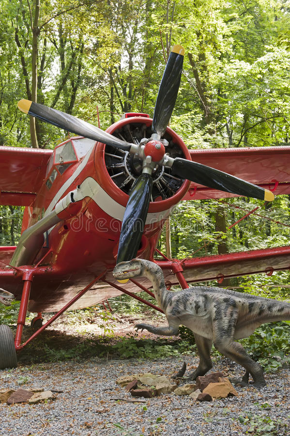Dinosaur and biplane. View of the dinosaur and the classic biplane in the forest royalty free stock photos