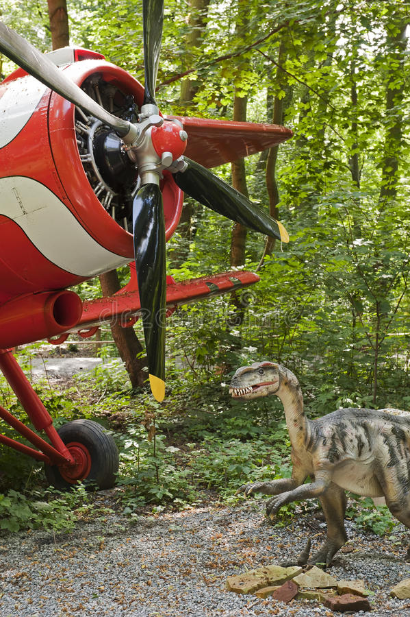 Dinosaur and biplane. View of the dinosaur and the classic biplane in the forest royalty free stock photography
