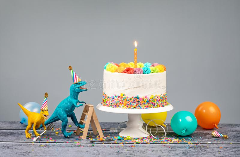 Dinosaur Themed Birthday Party with Cake. Hungry toy dinosaurs wearing hats and holding forks next to a birthday Cake on a gray background stock photography