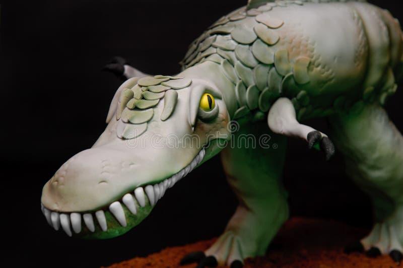 Dinosaur Cake. Close up of a handmade dinosaur cake with big teeth on a black background stock photo