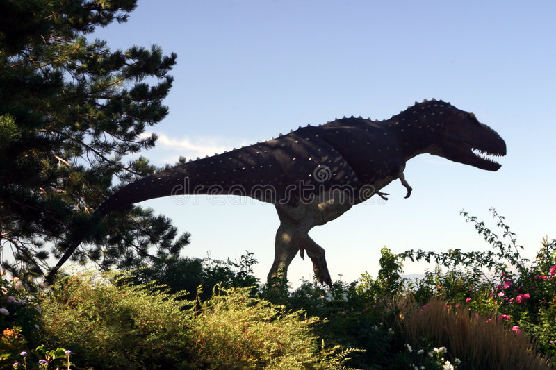 Dinosaur in the Garden. A replica of a dinosaur stands in the Salt Lake city arboretum and gardens stock photography