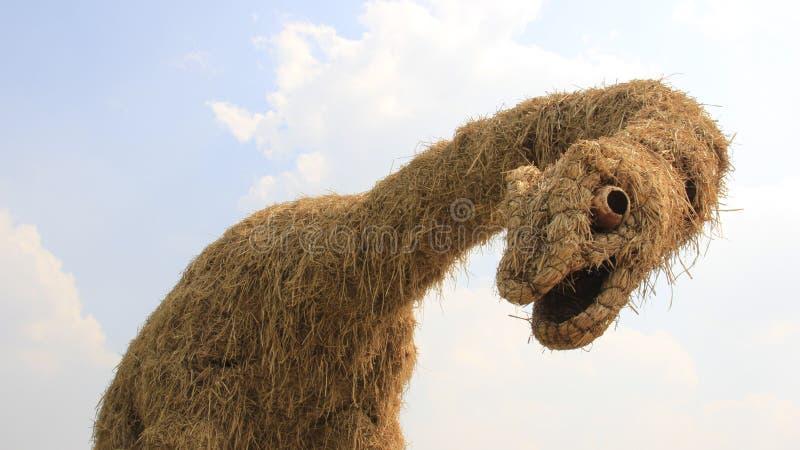 Dinosaur statua Robić Sucha słoma I Chmurny niebo zdjęcie stock