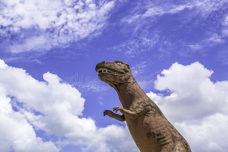 Dinosaur statue with blue sky. Dinosaur statue standing with blue sky background stock photos