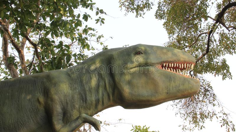 Dinosaur Statue With Plants And Green Leaves. Dinosaur statue with  tree and  leaf in summertime.  march 2019 Khon Kaen Thailand royalty free stock photography