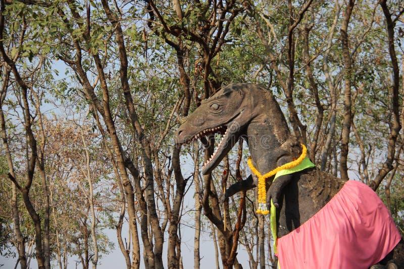 Dinosaur Statue With Plants And Warm Sunlight. Dinosaur statue public art with cassia fistula tree and pink silk march 2019 Khon Kaen Thailand stock photography