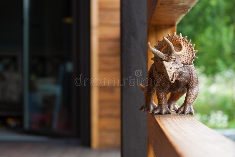 Dinosaur toy triceratops strolls along the terrace. Walking the dinosaur on the railing stock image
