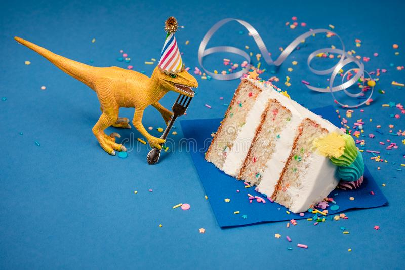 Dinosauriefödelsedagparti med skivan av kakan royaltyfria bilder
